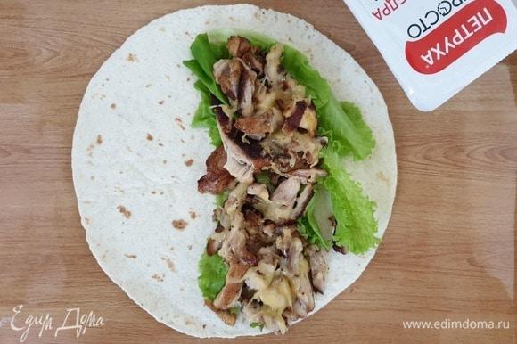 Можно собирать наше блюдо. На тортилью выкладываем листья салата, затем курицу с сыром.