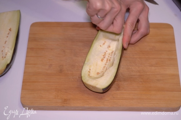 Разрезаем баклажаны вдоль на две части и вынимаем мякоть из каждой половинки.