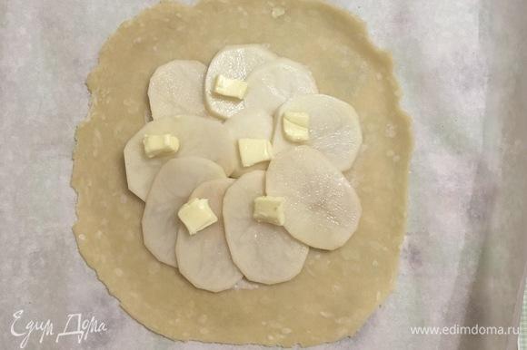 Тесто достать из холодильника и разделить на две половины. Получается две небольшие галеты. Каждую часть теста раскатать в круглый пласт толщиной 3–5 мм. Выкладываем картофель, немного солим, и сверху — несколько кусочков сливочного масла, чтобы галета была сочная.
