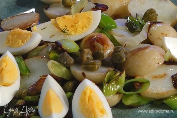 На тарелку выложить картофель, порей, яйца и каперсы. Полить половиной заправки.