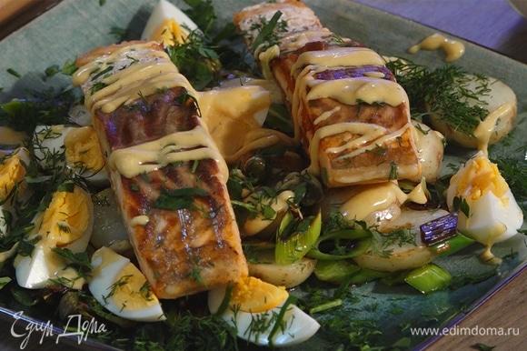 На овощи выложить готовые стейки. Блюдо украсить зеленью и оставшейся заправкой.