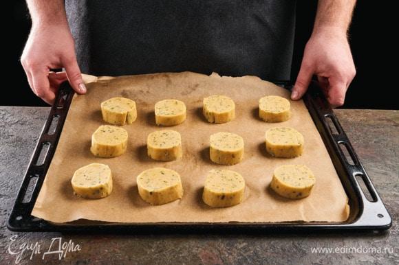 Разрежьте сформированное тесто на пласты по 2 см. Застелите противень пергаментной бумагой, выложите печенье. Поставьте печенье в разогретую до 180°С духовку и выпекайте 10 минут. Вытаскивайте сразу, как только начнут румяниться бока.