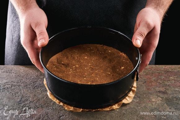 Дно разъемной формы застелите пергаментом, выложите сливочную крошку, равномерно распределите по дну. Поставьте в духовку, разогретую до 180°С, на 10–15 минут.