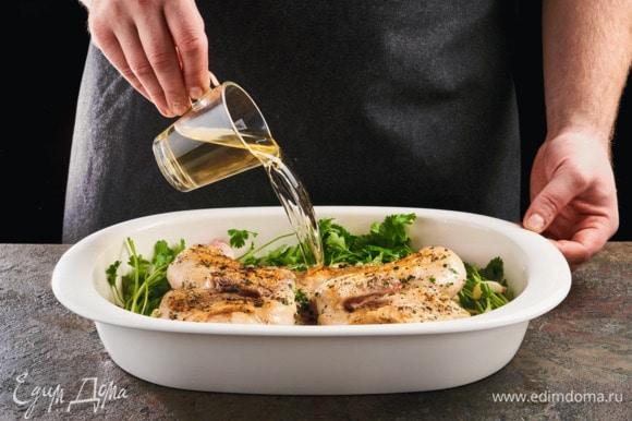 В форму выложите цыпленка, налейте белое вино. Добавьте веточки кинзы и зубчики чеснока.