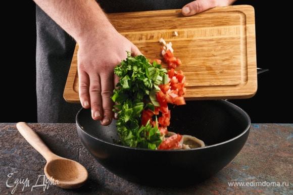 Добавьте в сковороду помидоры, зелень, перемешайте и обжаривайте до готовности кальмаров.