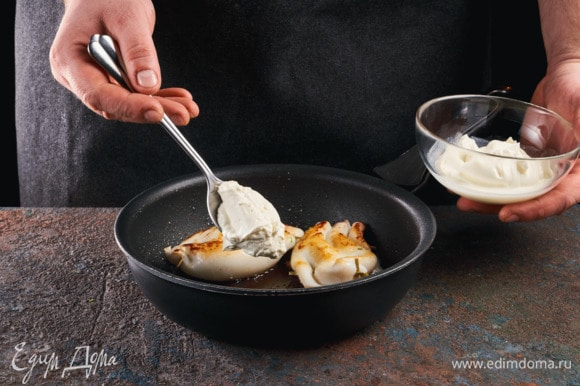 Выложите кальмаров на сковородку, смазанную маслом. Сметаной обильно смажьте тушки. Тушите 2–3 минуты.