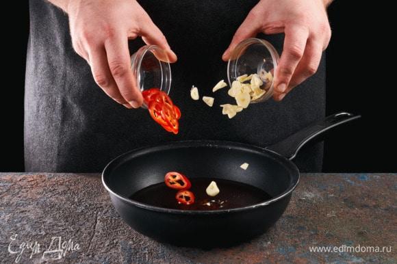 Чеснок и перец чили нарежьте кружочками. В сковороде слегка нагрейте оливковое масло, обжарьте в нем чили и чеснок до золотистого цвета.