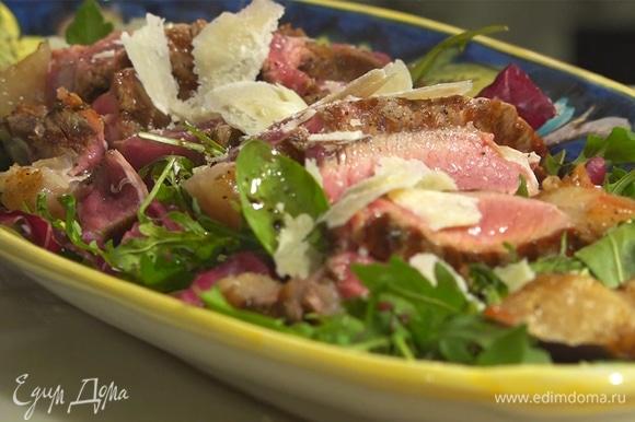 Нарезать мясо на куски толщиной полсантиметра, выложить на салат, посыпать пармезаном, сверху полить бальзамическим уксусом.