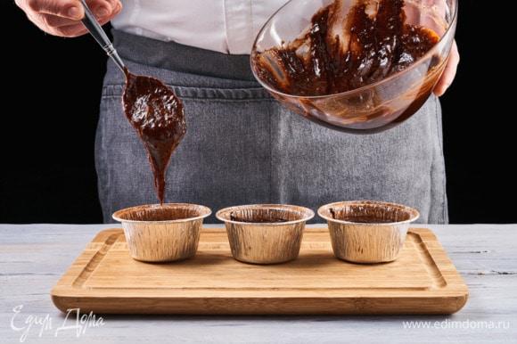 Заранее разогрейте духовку до 200°C. Смажьте формочки для кексов растительным маслом и слегка посыпьте какао-порошком. Наполните формы тестом и отправьте в духовой шкаф на 9 минут.