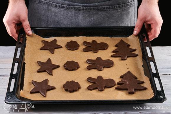 Раскатайте тесто на пекарской бумаге и вырежьте при помощи формочек новогодние фигуры — елочки, звезды, домики. Отправьте в заранее разогретую до 190°C духовку. Выпекайте около 9 минут.