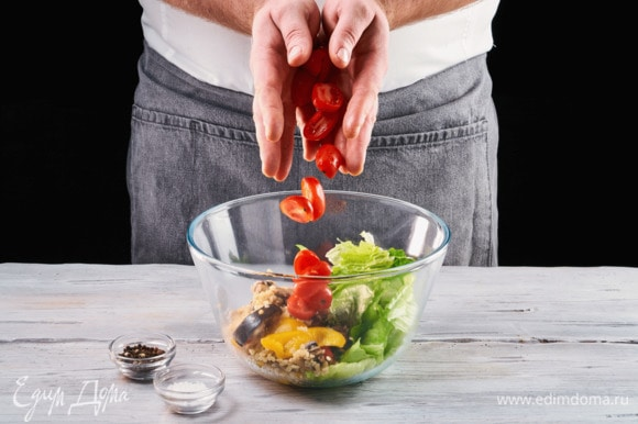 Вымойте салатные листья и выложите их в салатник. Добавьте разрезанные пополам помидоры черри.