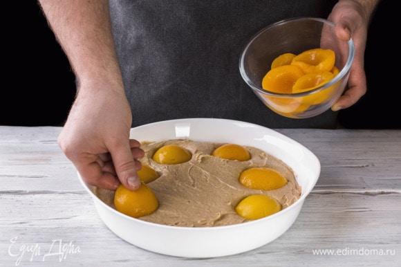 Сверху выложите по кругу персики. Выпекайте в духовке при 180°С около 45–50 минут.