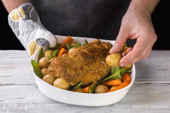 Через полтора часа достаньте из духовки, уберите фольгу, выложите по бокам буженины беби-картофель, морковь и стручки гороха. Полейте их маслом и поставьте в духовку еще на 20 минут.