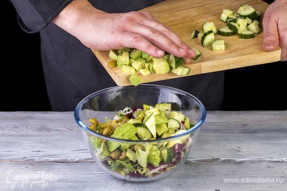 Добавьте оливки, авокадо и огурец.