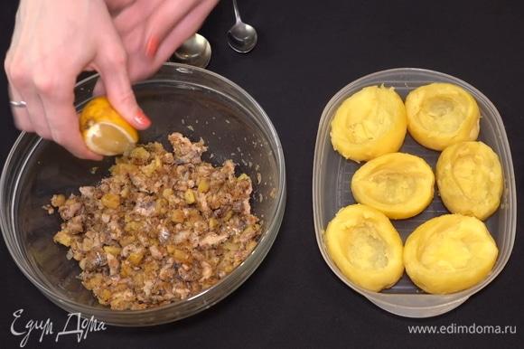 Поливаем начинку лимонным соком и заполняем углубления в клубнях.