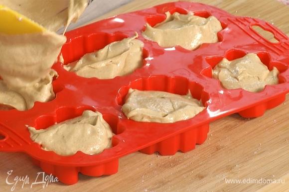 В силиконовую форму для выпекания кексов влить тесто, равномерно распределить.
