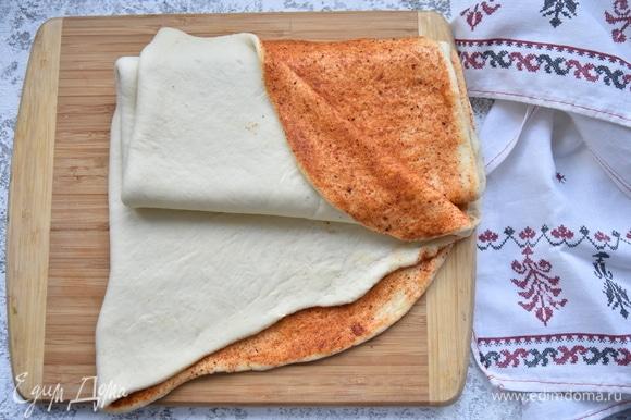 Раскатайте тесто в прямоугольник, толщиной 5 мм. Смажьте равномерно растительным маслом, посыпьте смесью паприки с чесноком и руками распределите смесь по всему периметру.