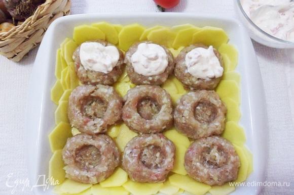 В мясных шариках делаем углубления и выкладываем сметану с помидорами.