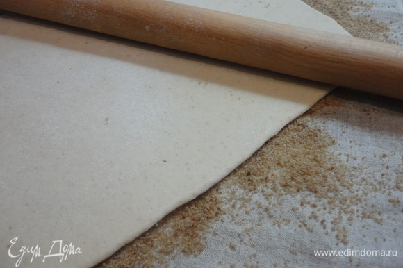 Затем достать тесто из морозильной камеры. Поверхность теста слегка смочить водой и перевернуть на сухари. Сверху слегка прокатать скалкой.