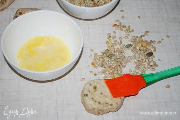 Сформируйте булочки, смажьте поверхность яйцом, посыпьте оставшимися семечками и слегка вдавите их в тесто.