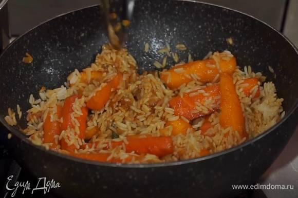 Бланшированную морковь переложить шумовкой в вок с овощами, влить соевый соус, кленовый сироп, все перемешать, добавить рис и помешивая, обжаривать несколько минут, затем снять с огня.