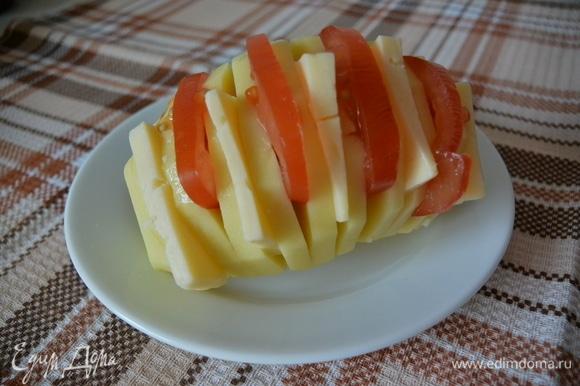 Нарезать картофель не до конца, поочередно положить сыр и помидоры.