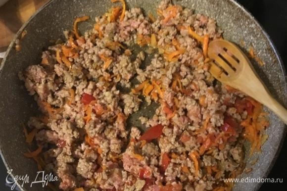 Добавить к луку натертую морковь, немного обжарить. Добавить сюда же фарш, томаты, перемешать, посолить, поперчить.