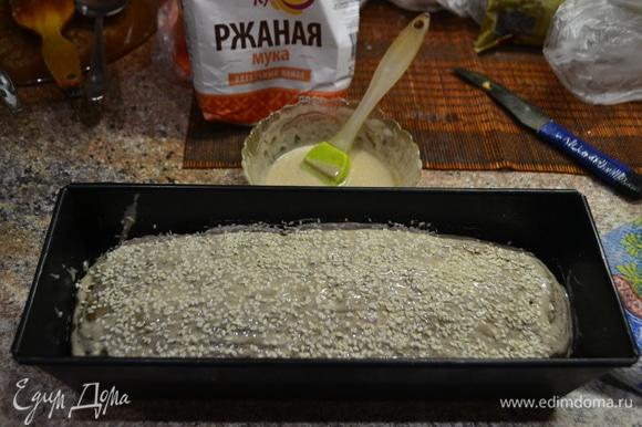 Далее выложить тесто в форму и на час оставить в теплом месте. Перед отправкой в духовку смазываю верх заготовок закваской, разведенной в воде. Сверху сразу посыпать кунжутом. Отправляем в разогретую до 200°C духовку на 45 минут. Также следите, когда образуется корочка и зубочистка будет сухой при прокалывании хлеба.
