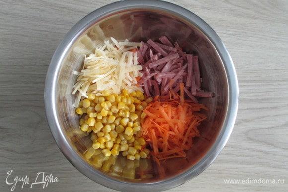 Из банки с консервированной кукурузой слейте жидкость. Сырую морковь натрите крупно, так же натрите полутвердый сыр. Колбасу нарежьте соломкой.