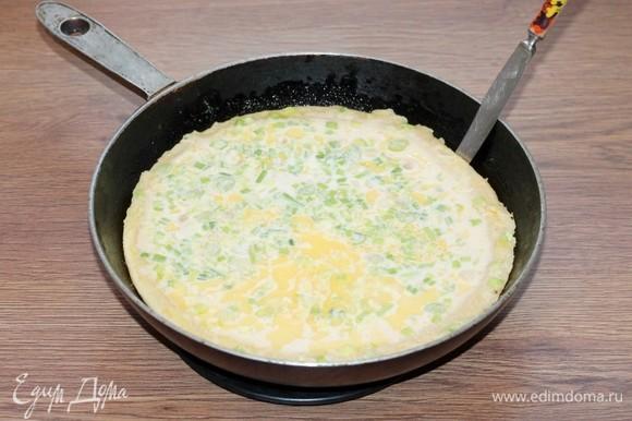 Когда масло начнет пениться, влить в сковороду тесто. Жарить на среднем нагреве минут 6 или до полуготовности. Если сковорода не антипригарная, силиконовой лопаткой или тупым ножиком, осторожно отодвинуть массу от стенок, чтобы не прилипало тесто.