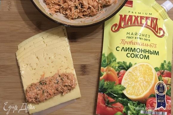 Сыр твёрдый лучше взять уже в тонкой нарезке. Выкладываем 1 ст. л. начинки на пластину сыра, сворачиваем в рулетик.