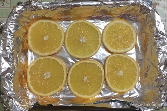 Выстелить фольгой форму для запекания, нарезать апельсин кружками и выложить на дно формы, делая подушку для курицы.
