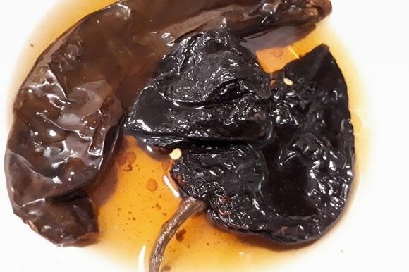 Замочите 1 перец чили пасилья и 2 перца чили анчо в горячей воде и оставьте до размягчения примерно на 15 минут.