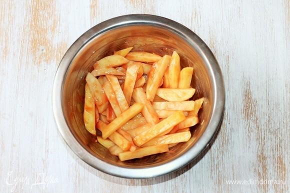 Смешиваем в миске прессованный чеснок, хлопья чили, кетчуп, соль и кукурузный крахмал. Добавляем картофель и хорошо перемешиваем.