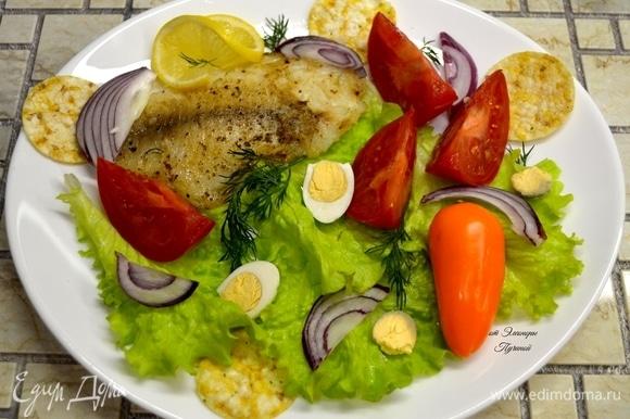 Ингредиенты нарезать произвольно, выложить на листья салата, положить рыбу.