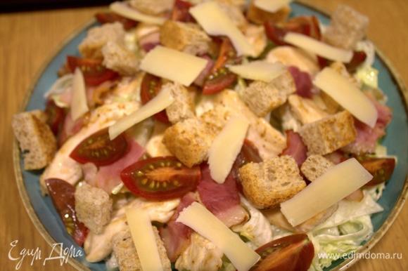 Перенести дольки на блюдо и с помощью овощечистки посыпать слайсами твердого сыра.
