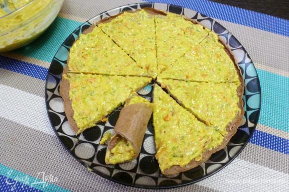 Пока остывают печеночные блинчики, надо будет приготовить начинку. Понадобится сливочный сыр, чеснок, немного майонеза, зелень петрушки, обжаренные лук с морковью. Измельчить все блендером до состояния пасты. Каждый печеночный блинчик намазать тонким слоем приготовленного паштета. Разрезать блин на 8 частей и каждый скрутить рогаликом. Отправить закуску в холодильник для охлаждения.