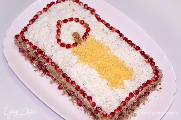 Посыпаю салат отварным белком, пропущенным через мелкую терку, чтобы структура поверхности была однородной и походила на полотно или фон. Украшаю бока смесью из гранатовых зернышек и молотых грецких орехов. Этот процесс похож на украшение тортов бисквитной крошкой. Для свечи понадобится желток, натертый на мелкой терке, опять же немного грецких орехов или часть ореха и гранатовые зернышки, чтобы нарисовать пламя. Всем приятного аппетита и счастливого Рождества! :)