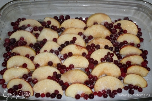 В большую глубокую форму для запекания выкладываем нарезанные ломтики яблок. Добавляем ягоды клюквы. Затем добавляем сахар и 1/2 ст. л. соли.