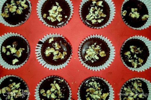 В формы для кексов вложить бумажные капсулы, заполнить капсулы на 3/4 тестом, сверху посыпать рублеными грецкими орешками.