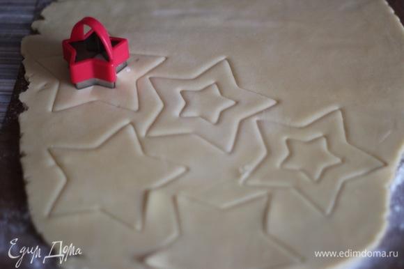 При помощи формочек вырезать печенья. В половине заготовок теста вырезать небольшими формами середину.