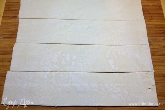 Размороженное слоеное тесто немного раскатываем и нарезаем полосками, шириной 6 см.