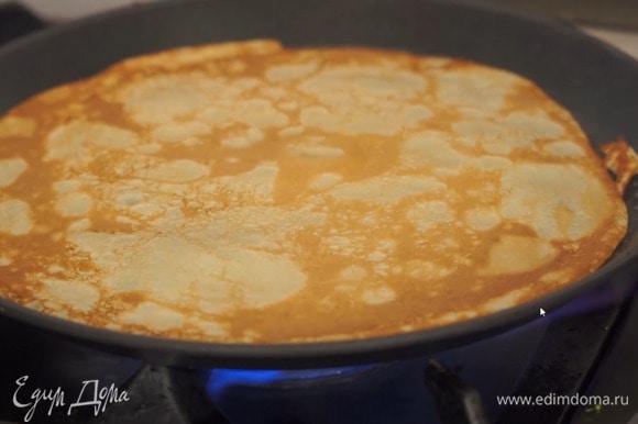 Разогреть блинную сковороду, смазать кисточкой оливковым маслом и испечь блинчики.