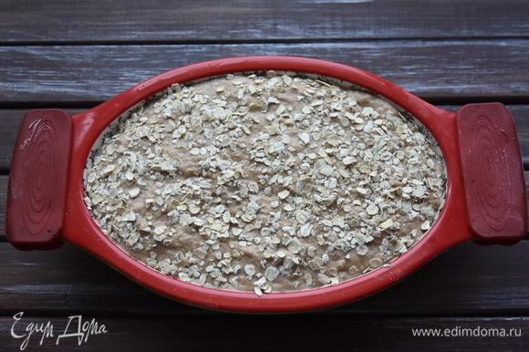 Выложить тесто в форму, смазанную растительным маслом. Сверху посыпать овсяными хлопьями. Духовку разогреть до 200°C и выпекать хлеб 40–45 минут. Дать ему немного остыть в форме, извлечь и полностью остудить на решетке.