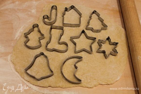 На доске раскатываем тесто толщиной примерно 5–6 мм. Вырезаем фигуры новогодними формочками.