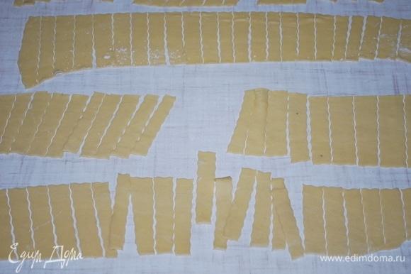 Раскатайте тесто, разрежьте на полоски примерно 4–5 см в длину.