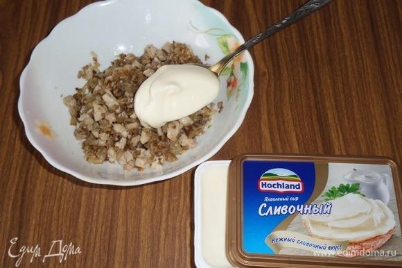 Курино-грибную массу выкладываем в чашку. Добавляем плавленый сливочный сыр Hochland и перемешиваем.