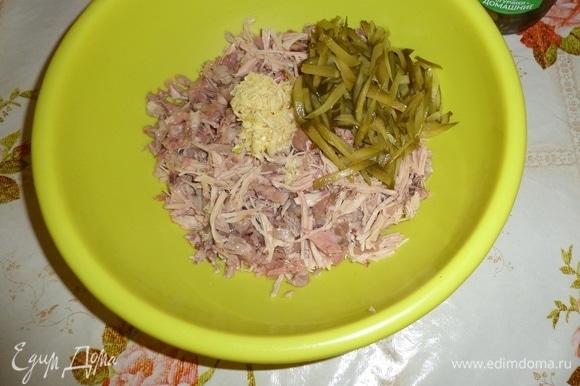 В глубокую чашку выкладываем нарезанное мясо и огурцы. Добавляем измельченный чеснок.