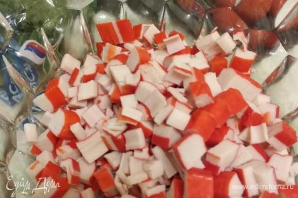 Нарезать кубиком крабовые палочки или крабовое мясо.