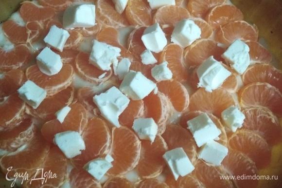 На тесто выложить дольки мандаринов и рубленное на кусочки сливочное масло.